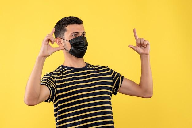 Jovem, de frente, com camiseta listrada em preto e branco mostrando o tamanho em fundo amarelo