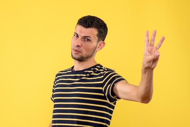Jovem, de frente, com camiseta listrada em preto e branco, mostrando três dedos em fundo amarelo isolado