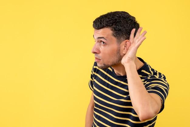 Jovem, de frente, com camiseta listrada em preto e branco, ouvindo algo sobre fundo amarelo isolado