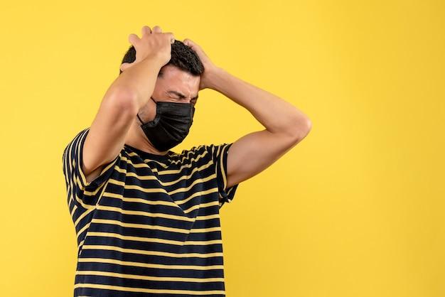 Jovem, de frente, com camiseta listrada em preto e branco, segurando a cabeça com dor em fundo amarelo