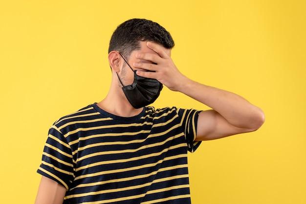 Jovem, de frente, com camiseta listrada em preto e branco, segurando a cabeça com fundo amarelo