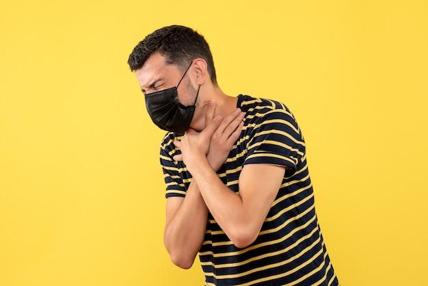 Jovem, de frente, com camiseta listrada em preto e branco, segurando a garganta com dor em fundo amarelo