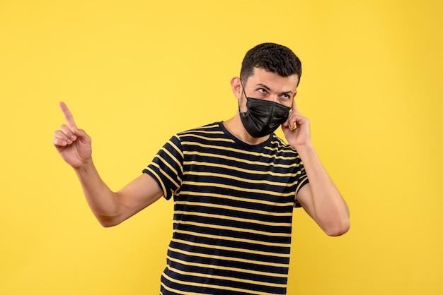 Jovem, de frente, com uma camiseta listrada em preto e branco, apontando para algo em um fundo amarelo isolado