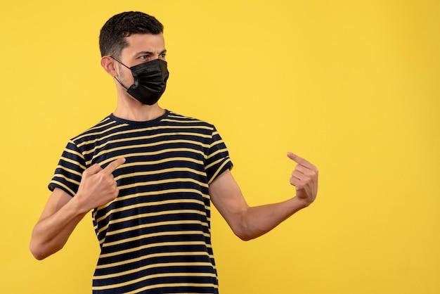 Jovem, de frente, com uma camiseta listrada em preto e branco apontando para si mesmo.