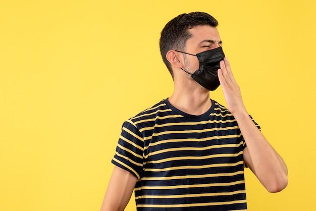 Jovem, de frente, com uma camiseta listrada em preto e branco bocejando em um fundo amarelo isolado