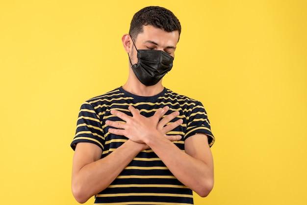 Jovem, de frente, com uma camiseta listrada em preto e branco, colocando a mão em seu peito sobre um fundo amarelo