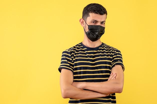 Jovem, de frente, com uma camiseta listrada em preto e branco, cruzando as mãos sobre um fundo amarelo isolado