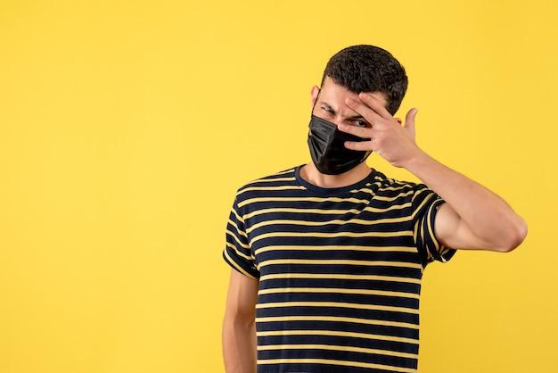 Jovem, de frente, com uma camiseta listrada em preto e branco, em pé no local de cópia de fundo amarelo