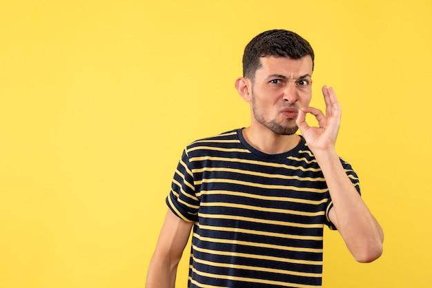 Jovem, de frente, com uma camiseta listrada em preto e branco, em pé sobre um fundo amarelo isolado