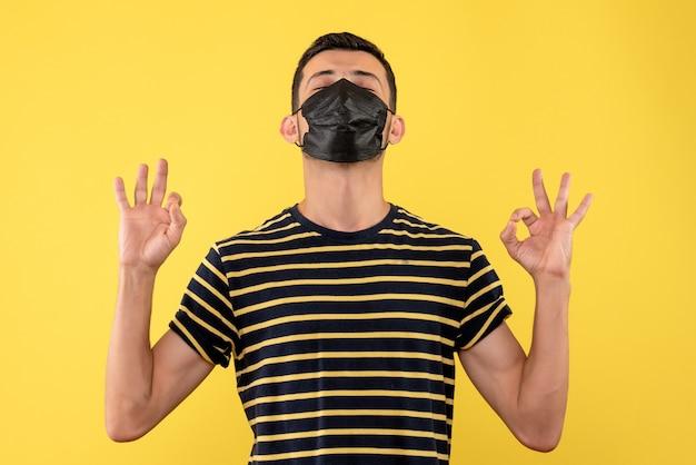 Jovem, de frente, com uma camiseta listrada em preto e branco, fechando os olhos em pé sobre um fundo amarelo
