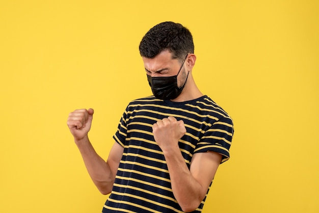 Jovem, de frente, com uma camiseta listrada em preto e branco, mostrando o gesto vencedor em um fundo amarelo isolado