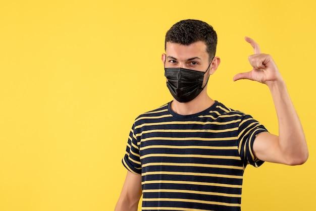 Jovem, de frente, com uma camiseta listrada em preto e branco mostrando o tamanho com os dedos em um fundo amarelo