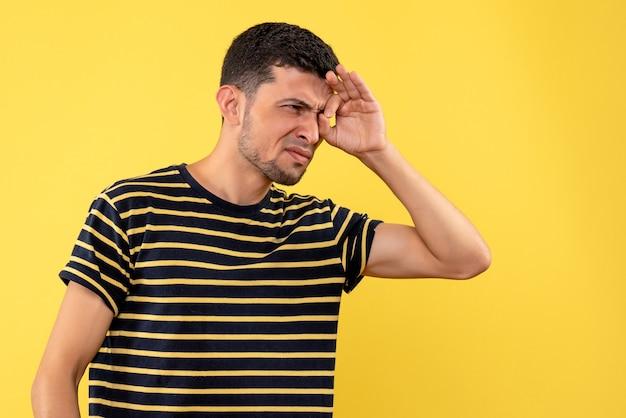 Jovem, de frente, com uma camiseta listrada em preto e branco, olhando para algo em um fundo amarelo isolado