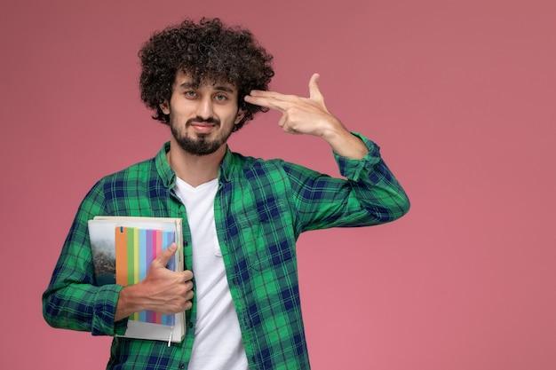 Jovem de frente mostra gesto de suicídio com cadernos