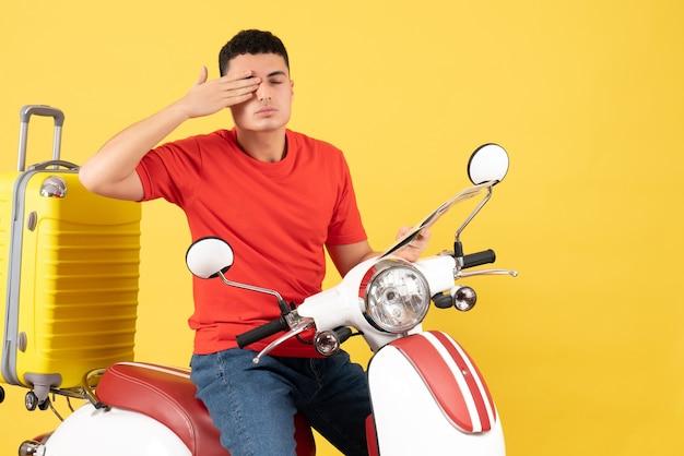 Jovem de frente para o ciclomotor cobrindo o olho com a mão