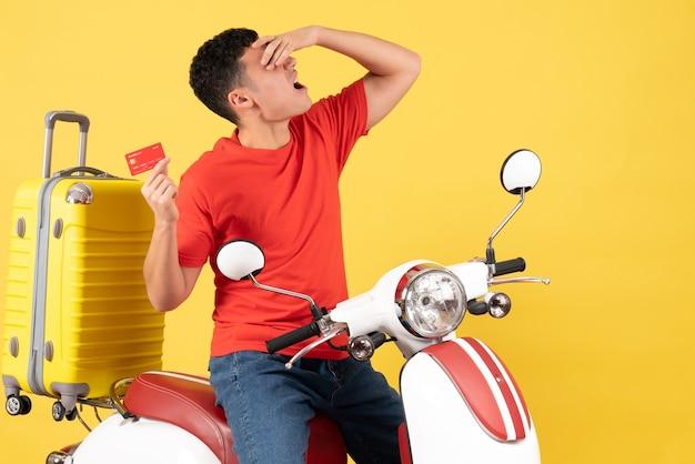 Jovem de frente para o ciclomotor segurando o cartão de crédito e colocando a mão no rosto