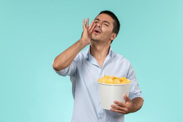 Jovem, de frente, segurando batatas cips e chamando alguém na parede azul. filmes remotos solitários.