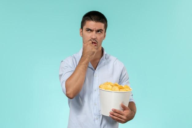 Jovem, de frente, segurando batatas cips e pensando na parede azul, cinema masculino remoto solitário