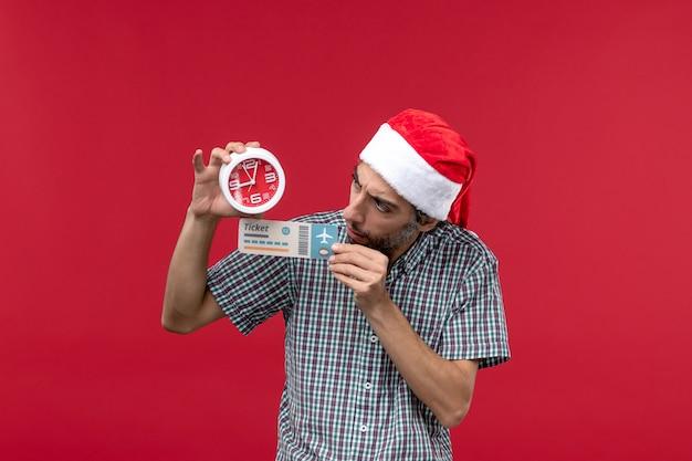Jovem, de frente, segurando o bilhete e o relógio na parede vermelha, tempo de emoções masculinas vermelhas
