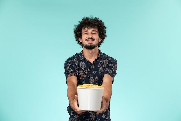 Jovem, de frente, segurando uma cesta com batata ciposa assistindo filme sorrindo em uma parede azul remoto filme cinema sala de cinema