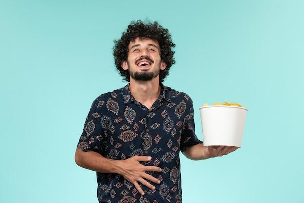 Jovem, de frente, segurando uma cesta com batata ciposa em uma mesa azul.
