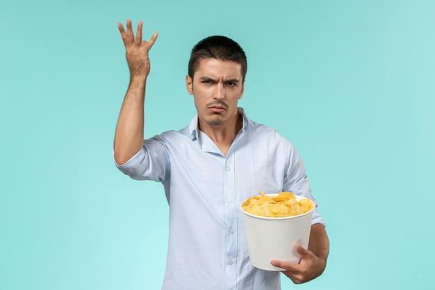 Jovem, de frente, segurando uma cesta com batata cips comendo e assistindo filme no cinema remoto solitário de parede azul claro