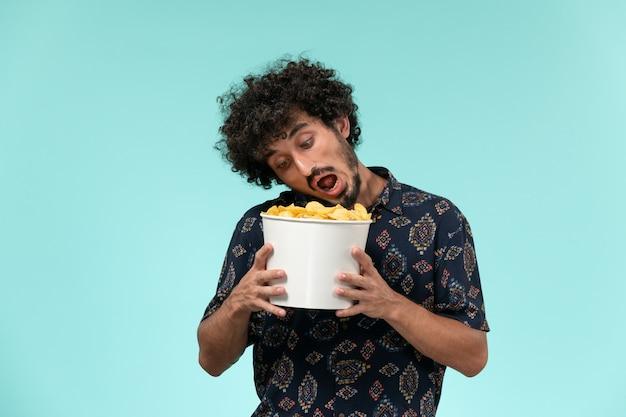 Jovem, de frente, segurando uma cesta com batatas cip na mesa azul. filme masculino, cinema, filmes remotos