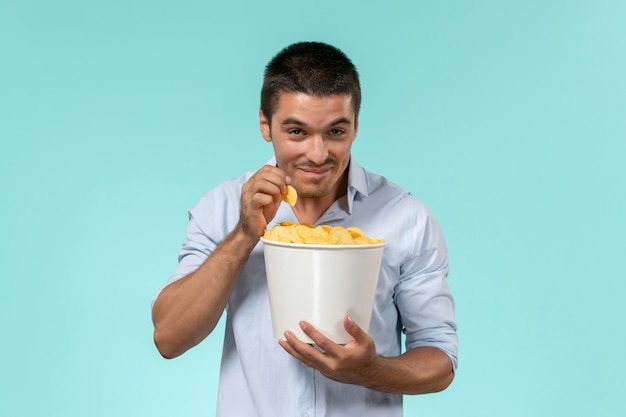 Jovem, de frente, segurando uma cesta com batatas cip no filme de parede azul-claro, cinema remoto