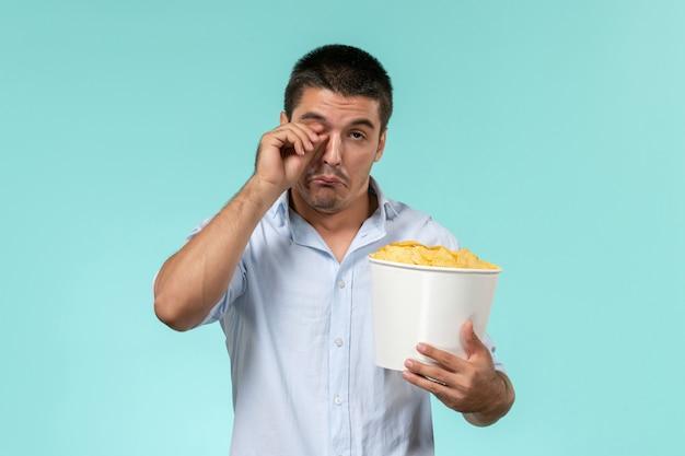 Jovem, de frente, segurando uma cesta com batatas cips e assistindo filme em filmes remotos de parede azul claro