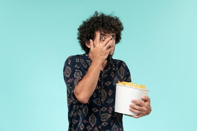 Jovem, de frente, segurando uma cesta com batatas cips e assistindo filme na mesa azul.