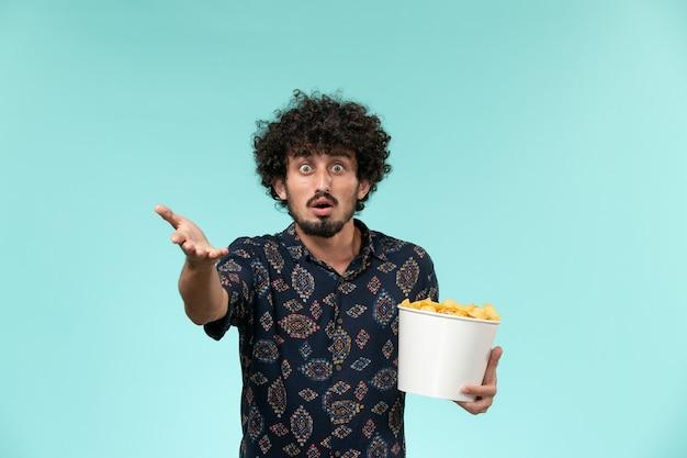 Jovem, de frente, segurando uma cesta com batatas cips e assistindo filme na parede azul filme masculino cinema filme remoto