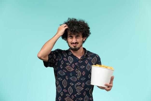 Jovem, de frente, segurando uma cesta com batatas cips e assistindo filme na parede azul.