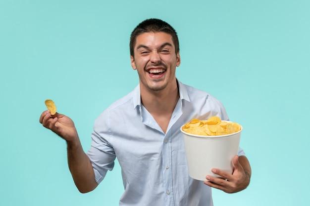 Jovem, de frente, segurando uma cesta com batatas cips e rindo no cinema remoto de filme de parede azul claro