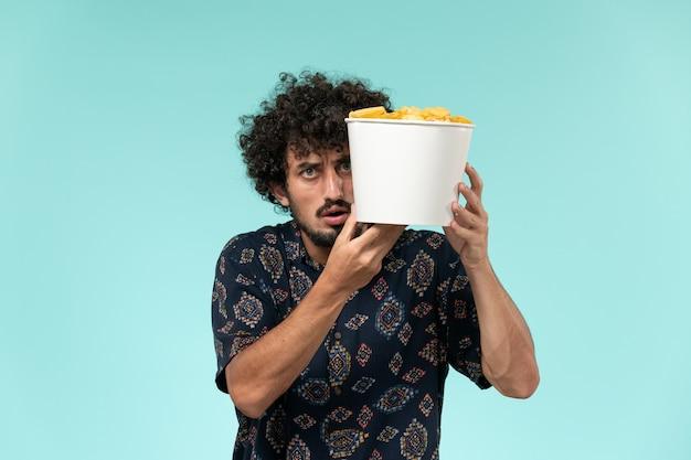 Jovem, de frente, segurando uma cesta com batatas cips em filmes de cinema remoto de parede azul