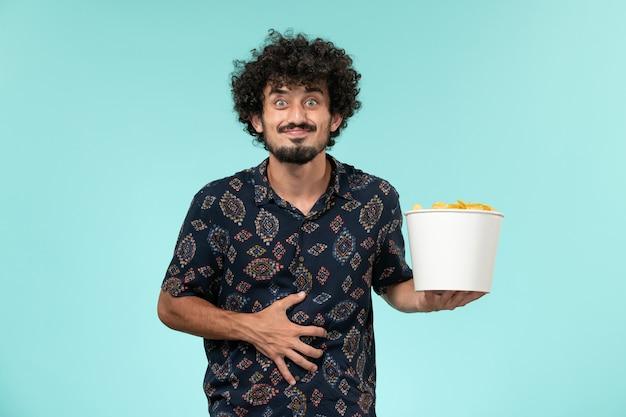 Jovem, de frente, segurando uma cesta com batatas cips em um controle remoto de filme de cinema masculino de parede azul