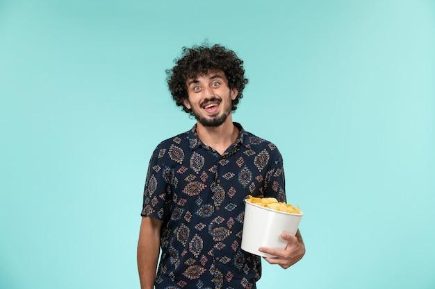 Jovem, de frente, segurando uma cesta com batatas cips na parede azul masculino filme cinema filme remoto