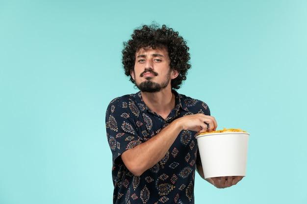 Jovem, de frente, segurando uma cesta com batatas cips na parede azul remoto filme cinema cinematográfico