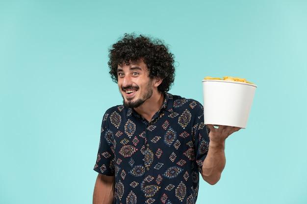 Jovem, de frente, segurando uma cesta com batatas fritas na parede azul-claro remoto cinema cinema filme cinema