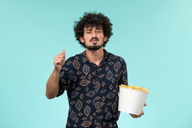Jovem, de frente, segurando uma cesta com cips em um filme de cinema remoto de parede azul