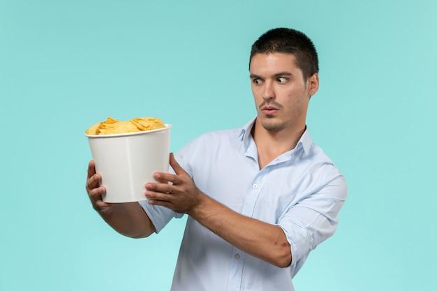 Jovem, de frente, segurando uma cesta com cips em um filme de parede azul claro.