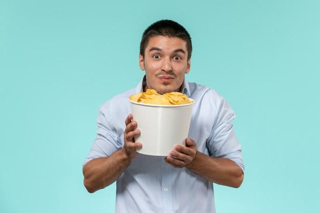 Jovem, de frente, segurando uma cesta com cips na mesa azul, filme remoto, cinema, cinema, cinema