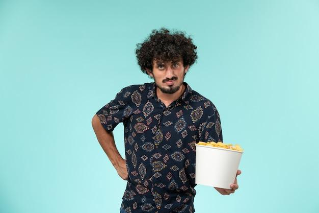 Jovem, de frente, segurando uma cesta com cips na parede azul remoto cinema filmes filmes