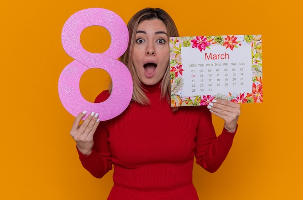 Jovem de gola alta vermelha segurando o calendário de papel do mês de março e o número oito