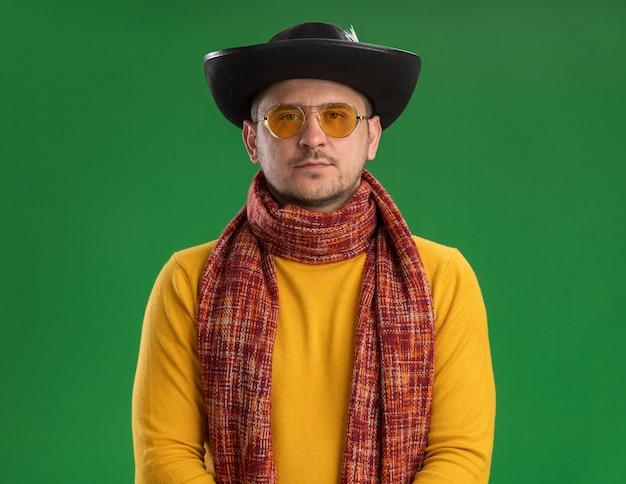 Jovem de gola olímpica amarela e óculos com lenço quente em volta do pescoço, chapéu preto com cara séria, conceito de feriado de ano novo, em pé sobre a parede verde