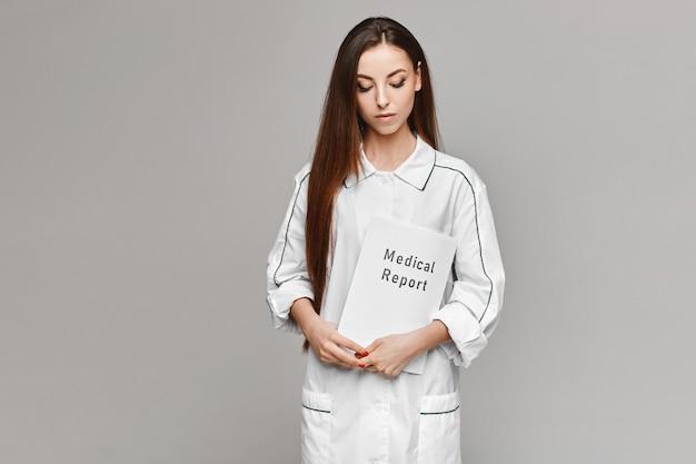 Jovem de jaleco branco médico posando com um relatório médico em suas mãos para o fundo cinza. copie o espaço para o seu texto e produto. conceito de saúde. modelo feminino na imagem de um médico
