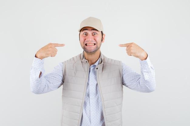 Jovem de jaqueta bege e boné sorrindo e apontando para si mesmo com o dedo indicador e olhando feliz, vista frontal.