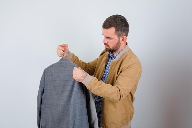Jovem de jaqueta, camisa, olhando para o terno, de pé de lado e parecendo melancólico.