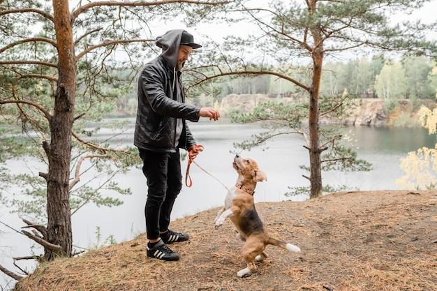 Jovem de jaqueta de couro e calça jeans preta dando algo saboroso para o lindo cachorro beagle de raça pura durante o frio.