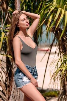 Jovem de jeans fica perto de palmeiras tropicais