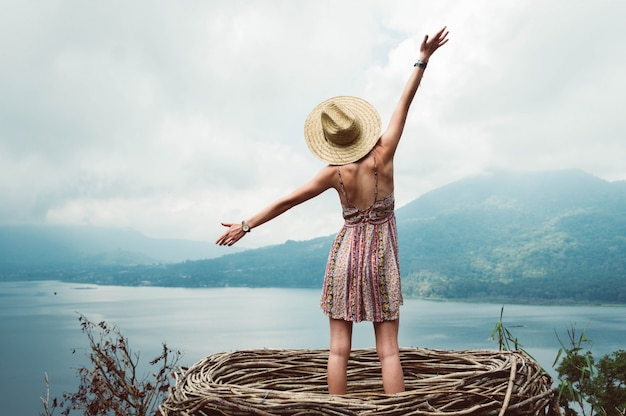 Jovem de liberdade despreocupada e feliz com os braços abertos no fundo da paisagem de montanha